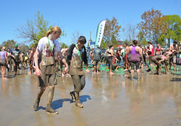 A very muddy couple walks past the shower area after the Mud Hero race in Toronto, many people are trying to get the mud off themselves using hoses and cold water