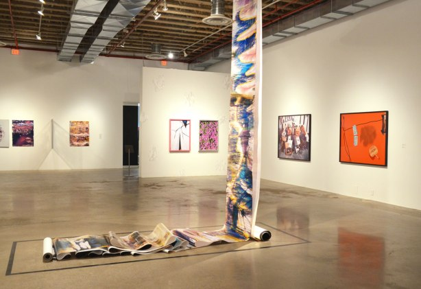 pictures on an art gallery wall.  In the middle of the room is a large roll of photographic paper that has been developed with streaks of colour.  It hangs from the ceiling and lays on the floor.