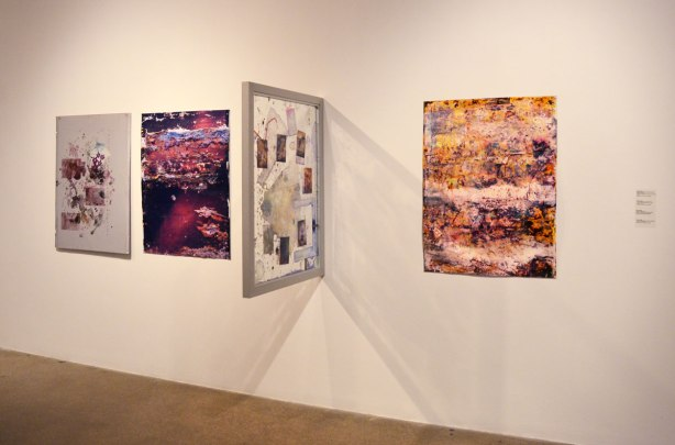 Four pictures on an art gallery wall, all abstract.  One of them protrudes from the wall at a 90 degree angle.