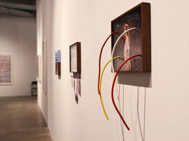 pictures on a gallery wall.  the picture in the foreground has 4 coloured wires protruding from it, 2 yellow and 2 red.