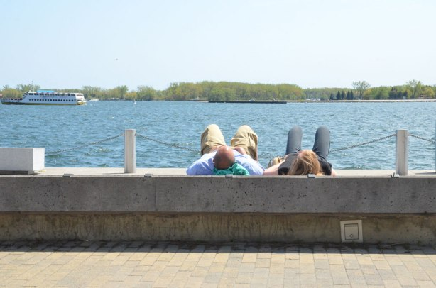 A couple is lying on their backs on a concrete bench beside lake Ontario.  Their legs are bent and feet are on the bench, feet towards the lake, head towards the camera.  You can see the backs of their heads.