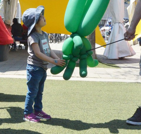 A child looks askance at thing made of green balloons.