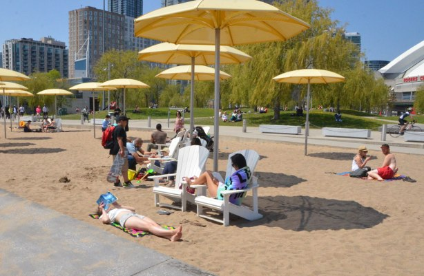 people lying in the sand or sitting on chairs, reading, talking, and enjoying the sunny afternoon under large yellow beach umbrellas.
