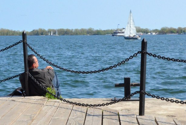 A man is sitting by the lake, his back to one of the posts supporting the chain links that separate the walkway from the water.