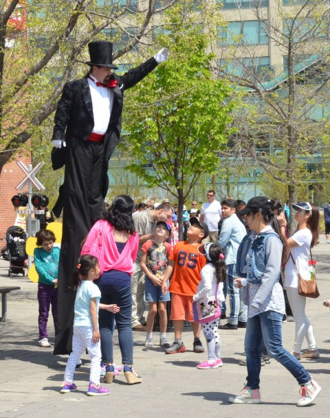 A man on stilts and wearing a black tux and tophat along with a red cumberbund and rose in his lapel is entertaining a group of people