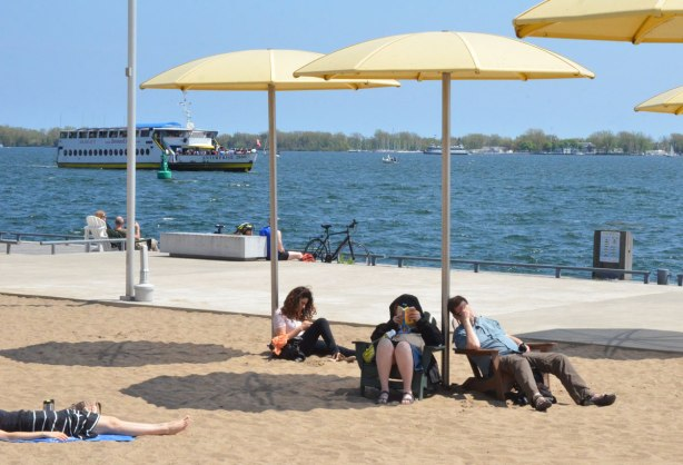 sitting under yellow beach umbrellas beside Lake Ontario