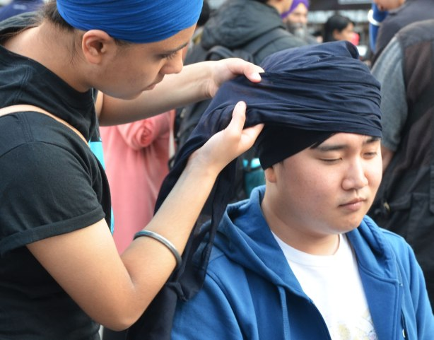 A young man having his head wrapped in a dark blue turban.  His eyes are closed.  Close up shot.