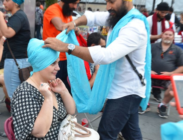 A man is wrapping a light blue turban around a young woman's head.