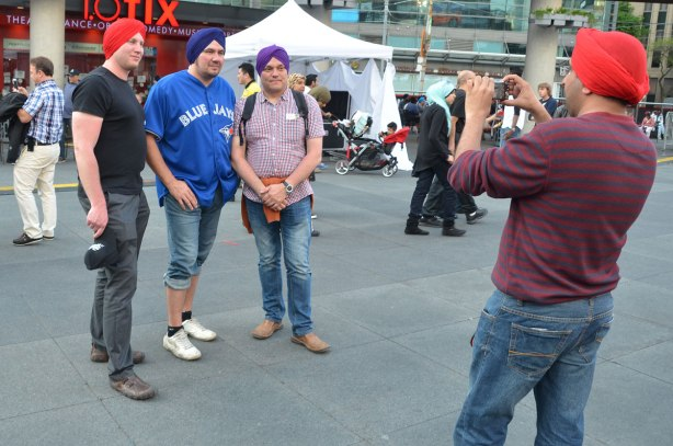 Three men in their new turbans are standing together while a fourth man is taking their picture.