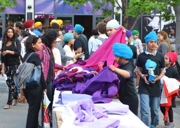 People in turbans are at a table sorting and folding purple and pink and blue fabric that is available for making turbans with.