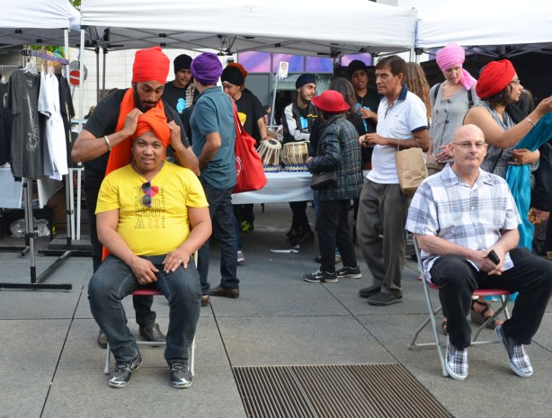 A man in a bright yellow T shirt is sitting in a chair while another man wraps an orange turban around his head.  To the right, an older man is waiting his turn to get a turban.