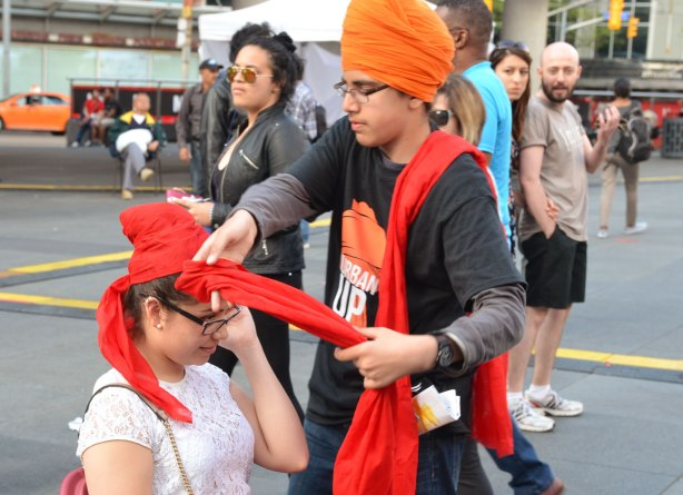Passersby have stopped to watch a an is wrapping a red turban around a young woman's head.