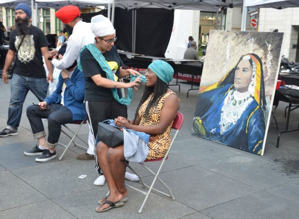 A black woman with long hair is having her head wrapped in a turquoise turban