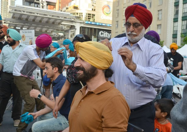 A man is grimacing while having a yellow turban wrapped around his head (and into his eyes) by an older Sikh man with a a dark red turban.