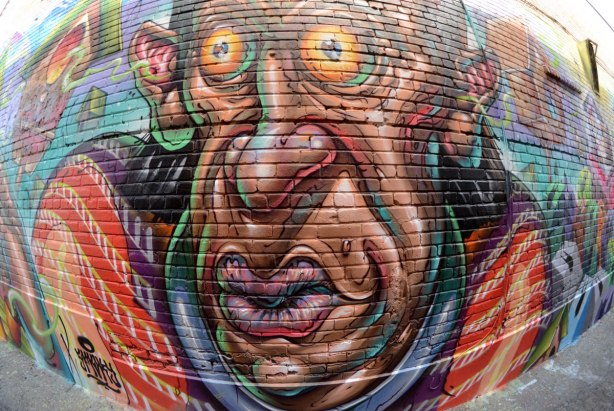 Part of a large colourful mural - a large wrinkly man's face with round bulging eyes