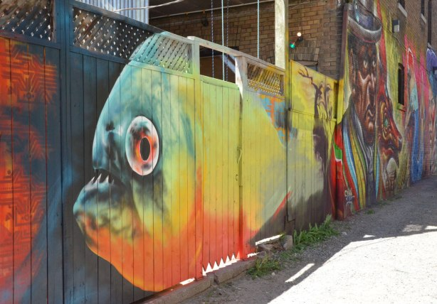 part of a large colurful mural, a large fish with a yellow and orange body and blue and green face, on a wooden fence