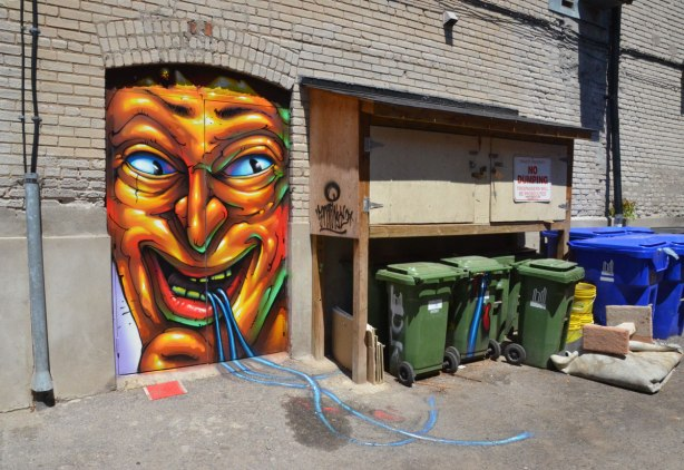 graffiti on a door of a large grotesque man's face with open mouth and what looks like blue ribbons coming out of his mouth, the blue ribbons continue on the concrete of the lane behind the door, and go towards the garbage bins beside the door.
