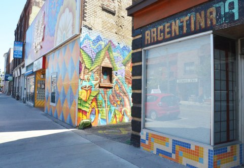 street scene on Dundas West, sidewalk and store fronts, with mural in the alley just showing betweenthe Lula lounge with its orange, blue and white tiled front and a store with the sign Argentina on it.