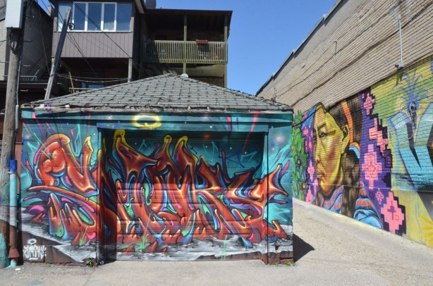 a garage door covered with a street art piece signed by smoky, a mural in the lane beside the garage is also visible