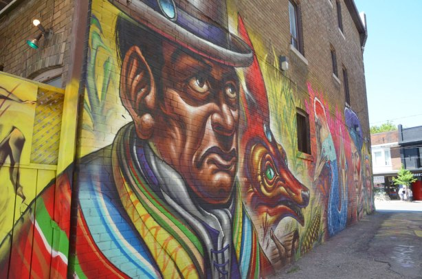 part of a large mural - a man wearing a bowler hat and a striped jacket, seen from the shoulders up.