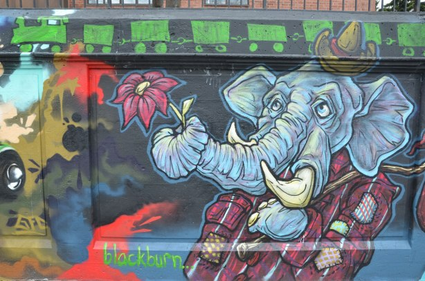 street art painting of an elephant standing upright, only upper part shown, wearing a plaid jacket, carrying a cane over his shoulder, a small hat on his head, and holding a flower in his trunk.   A green train runs across the top of the painting.   signed by blackburn