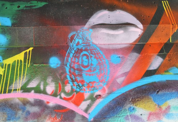 street art under a railway underpass - pink lips and a blue bomb with a smiling face on it  by spud