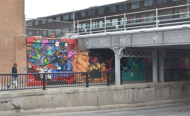 Man walking along a sidewalk towards a railway bridge.  One side of the underpass has been painted with street art pictures.