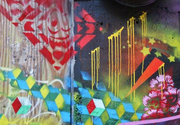 street art under a railway underpass - yellow stars, 3 D blocks and some pink flowers