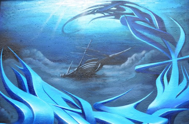 blue street art painting of a wrecked sailing ship partially submerged as she sinks stern first