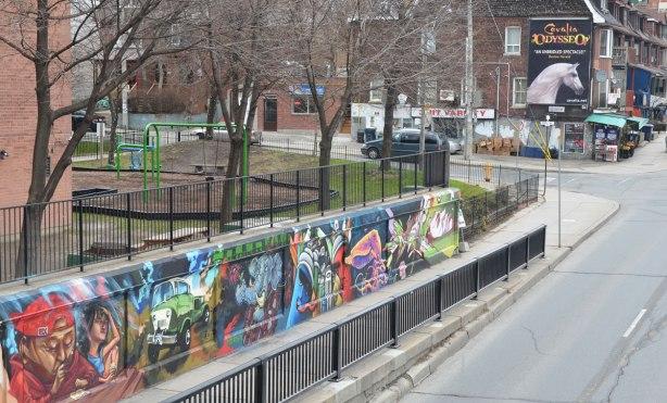 east side of mural under the railway bridge - series of street art paintings by different artists, playground behind, street scene beyond.