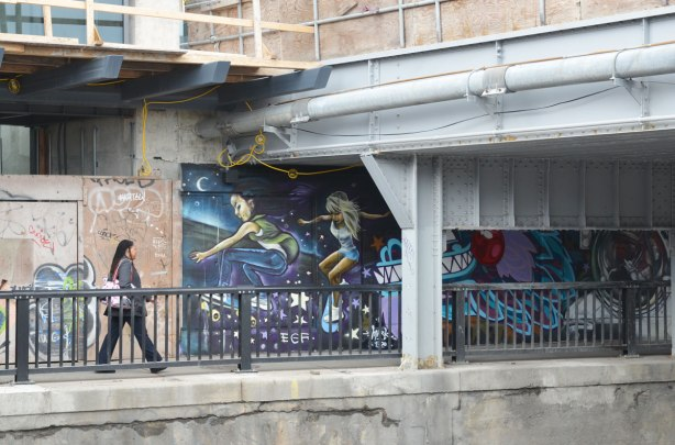 woman walking along a sidewalk under a railway bridge.  There is a graffiti picture of two people skateboarding beside her.