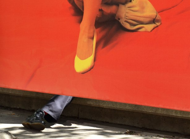 a man's leg and black boot stick out from under a picture of a woman's leg with a yellow shoe, on a bright orange background.  A man is sitting on a ledge behind the photo.