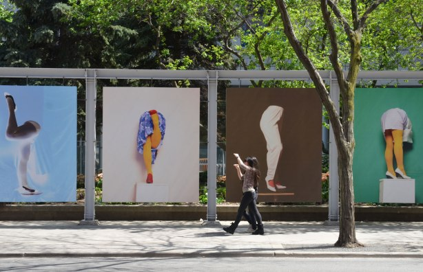 Two young women are alking past a few large, larger than life photos of legs.  The women have their arms up in the air.