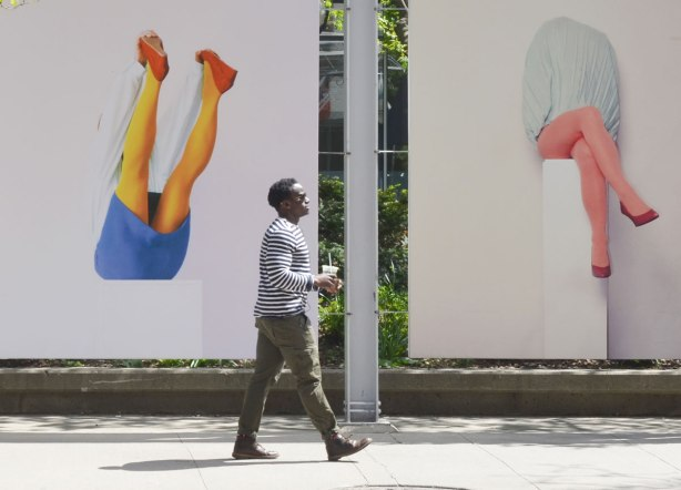A man in brown pants and a brown and white striped shirt is holding a drink in his hand as he walks past two large pictures of legs.