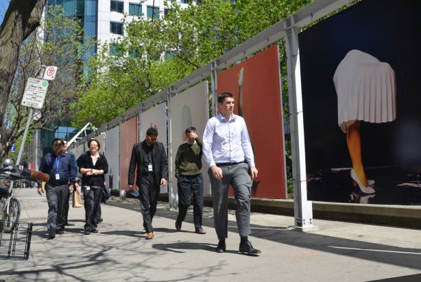 Six people walking on a sidewalk.  They are walking past a row of large pictures of legs in various strange poses on bodies with no upper parts.