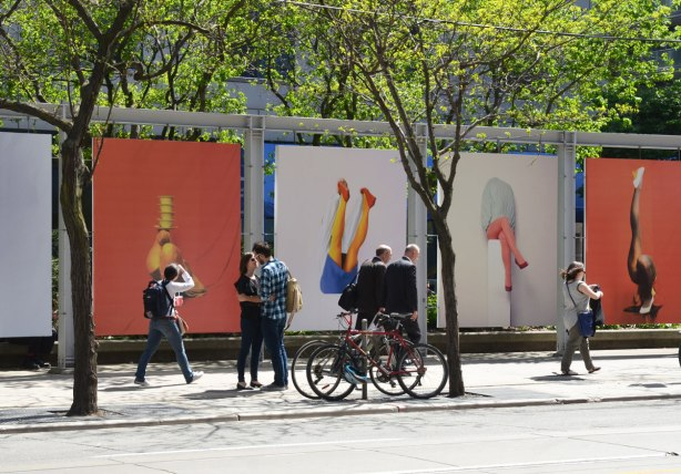 people in front of 4 large photos of legs by Isabelle Wenzel.  A couple are saying goodbye, two men in suits are walking together, a woman is looking at the pictures as she walks past and another woman is walking out of the photo on the right.