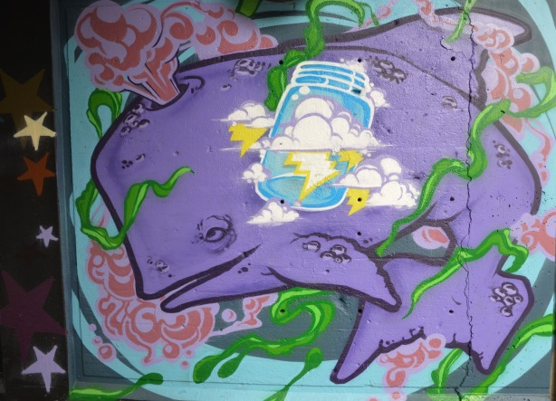 street art painting under a railway bridge - purple whale