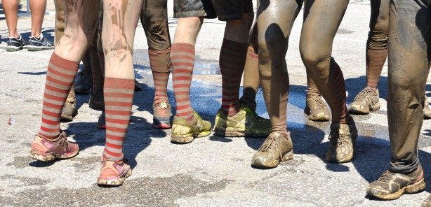 A row of muddy legs with very brown socks and filthy shoes, after the Mud Hero race