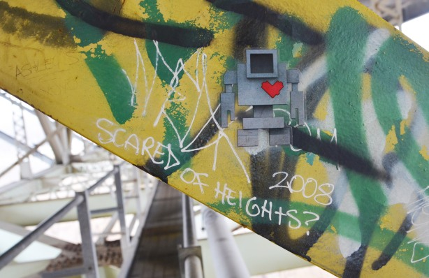 lovebot sticker on a yellow metal girder under a bridge