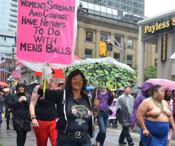 "Pride week, Dyke march, a woman is carrying a pink sign that says ""womens strength and courage has nothing to do with mens balls"""
