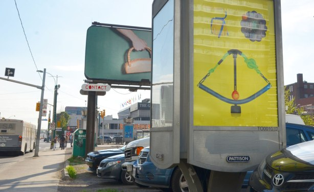 a small billboard in front and a larger, higher one in the background.   In the background is a woman's hand holding what looks like a handbag but the bag part is made of a loaf of bread.  In the foreground, yellow background with household objects arranged in a face like shape.