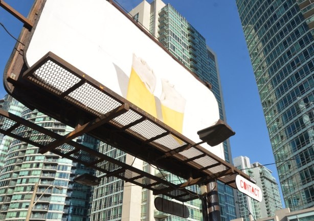 a billboard above a parking lot, condos in the background.   A pair of yellow rubber gloves with the openings turned into a cuff are all that in the image on the board