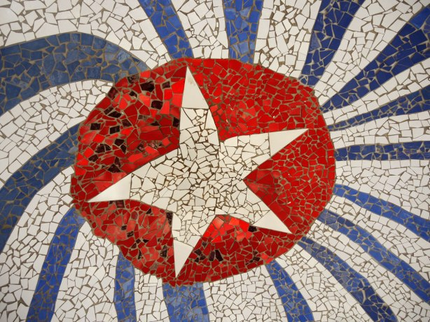 part of a large mosaic installation, ceramic tile pieces, white star in red circle surrounded by blue and white rays radiating from the center to look like the cuban flag