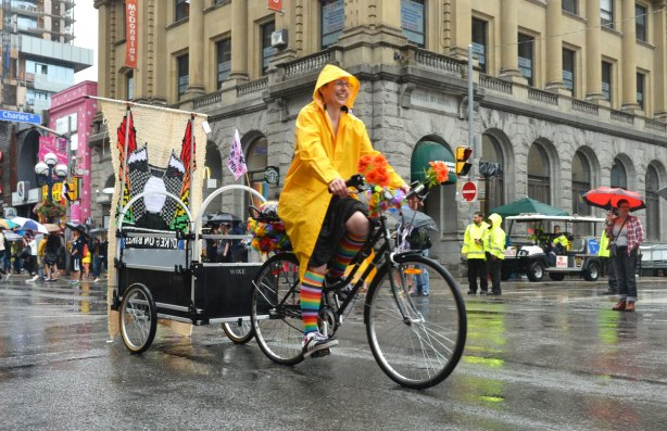 pride dyke march, dykes on bikes, woman in bright yellow raincoat rides a bicycle that is pulling a trailer