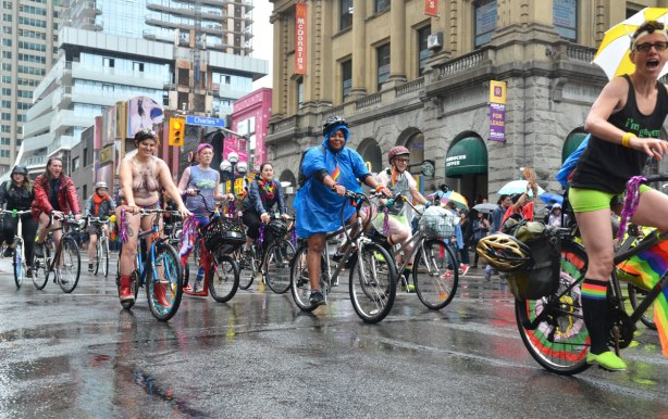 Group of women riding bikes in a parade on a rainy city street as part of a dyke march, pride week event.