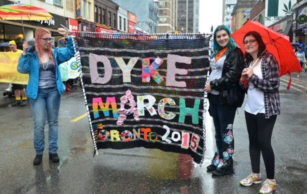 Three women are holding a large banner that says 'Dyke March Toronto 2015' that has been crocheted and sewn together.