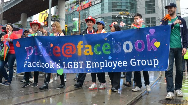 group of people holding up a blue banner that says Facebooks LGBT employee group
