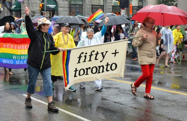 "A group of women walking in a dyke march on a rainy city street.  Two of the women are carrying a banner that says ""Fifty + Toronto"""