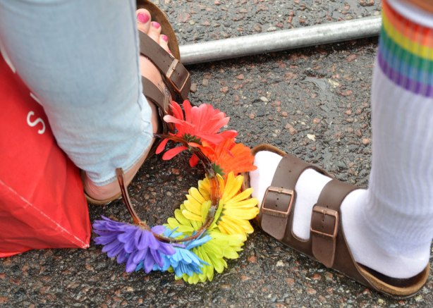 A flower head band has fallen to the ground and is beside two people's feet, both of whom are wearing sandals.