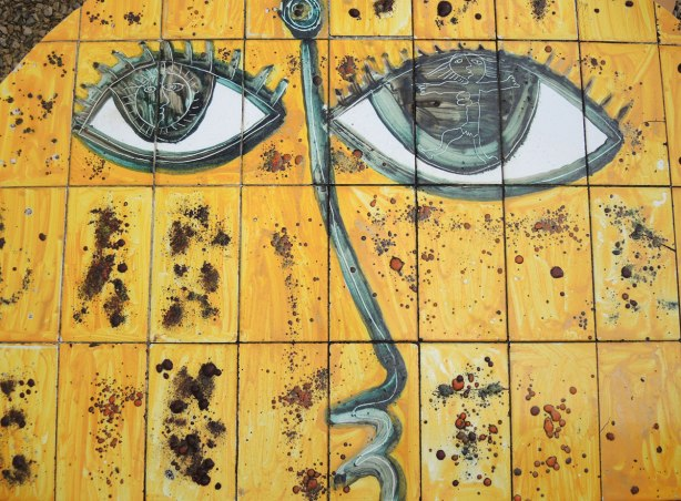 face made of bits of tile with some parts painted, part of a larger mosaic art piece, bright yellow face with dark blue eyes, green outline for the nose